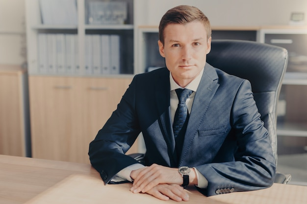 Professional male banker sits in cabinet, wears formal clothes