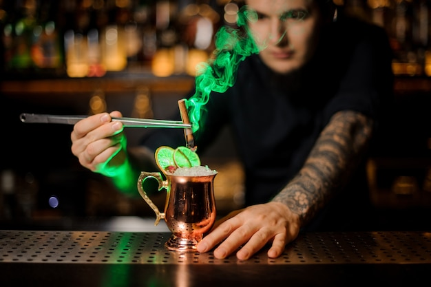 Professional male bartender adding to a cocktail in the cooper glass with a dried orange aromatic smoked cinnamon with tweezers on the bar counter