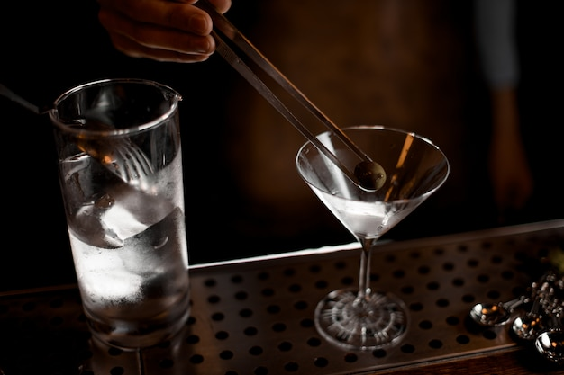 Professional male bartender putting an olive with tweezers to the martini glass