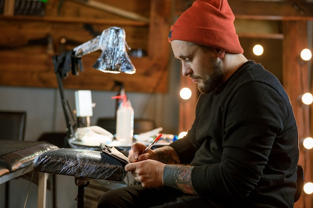 Professional male bearded caucasian tattoo master is working in cozy atmospheric studio