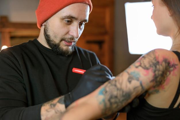 В уютной атмосферной студии работает профессиональный бородатый мастер кавказской татуировки.
