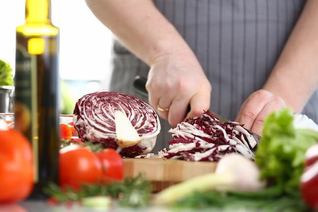 Профессиональный шеф-повар-мужчина нарезает фиолетовую капусту