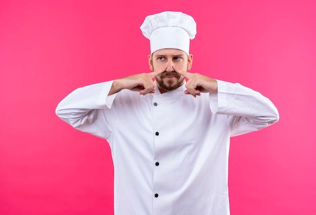 プロの男性シェフが白い制服で調理し、ピンクの背景の上の鼻、悪臭の概念を閉じる帽子を調理します。