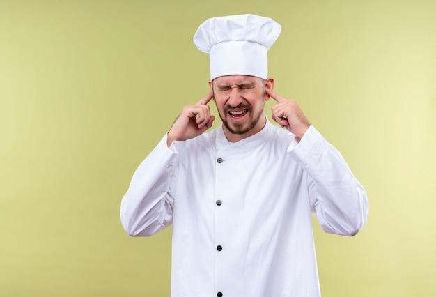 Профессиональный шеф-повар-мужчина в белой форме и поварской шляпе, закрывающей уши с раздраженным выражением лица от шума громкого звука, стоящего на зеленом фоне