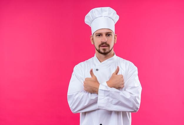 プロの男性シェフが白い制服を着て調理し、ピンクの背景の上に自信を持って立っている親指を現して帽子交差手