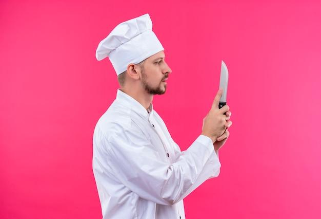 白い制服を着たプロの男性シェフが調理し、ピンク色の背景の上に横に立っているナイフを保持している帽子を調理します。