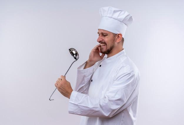 プロの男性シェフが白い制服を着て調理し、白い背景の上に立って取鍋を保持している緊張と神経質の痛烈な爪を保持している帽子を調理します。
