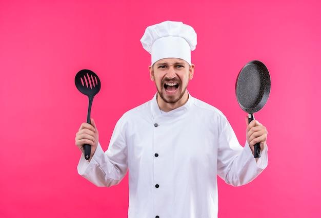 Профессиональный шеф-повар-мужчина в белой униформе и поварской шляпе держит сковороду и ковш, кричит с агрессивным выражением лица и разочарованно стоит на розовом фоне