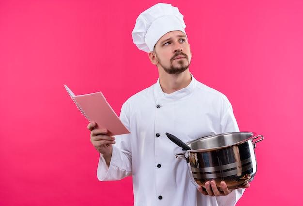 プロの男性シェフが白い制服を着て調理し、鍋とピンクの背景の上に立って選択をしようと考えてノートを見上げているノートを保持している帽子を調理します。
