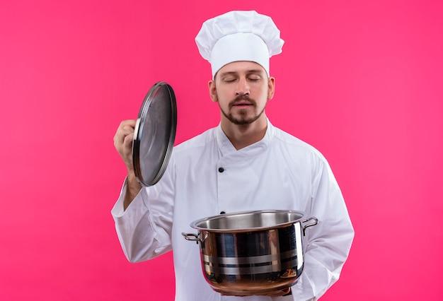 白い制服を着たプロの男性シェフが調理し、パンをかざして帽子をかぶってピンクの背景の上に立って食べ物の心地よい香りを吸い込む