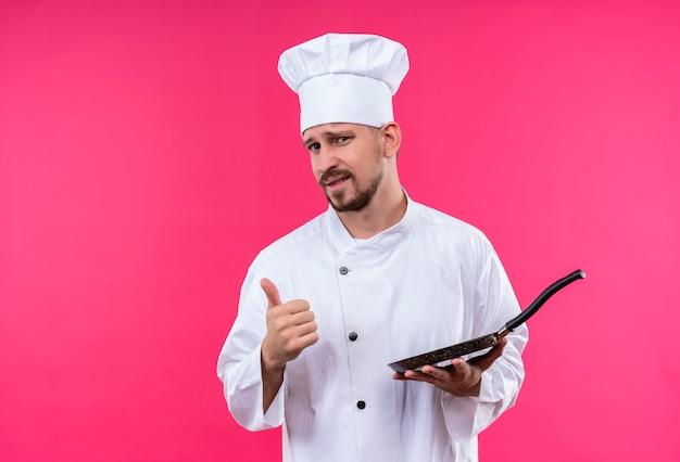白い制服を着たプロの男性シェフが調理し、ピンクの背景の上に立っている親指を示す自信を持って笑顔でカメラ目線のパンを持って帽子を調理します。