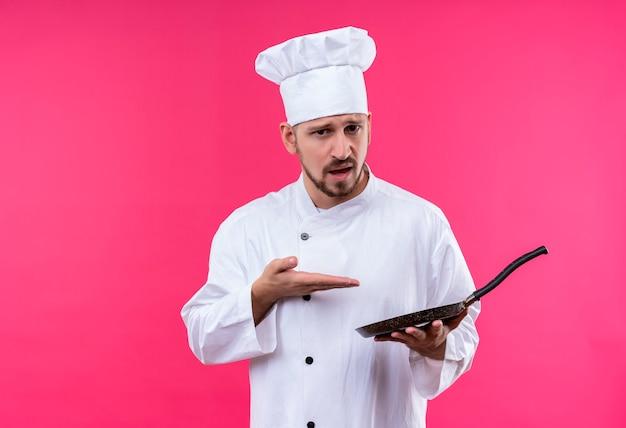 Профессиональный шеф-повар-мужчина в белой форме и поварской шляпе держит кастрюлю, указывая на нее рукой, глядя в камеру со скептическим выражением лица, стоящего на розовом фоне