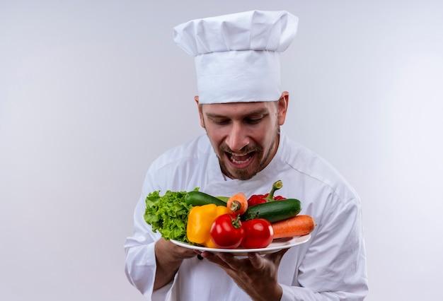 白い制服を着たプロの男性シェフが調理し、白い背景の上に感情的で心配して立っている野菜を見てプレートを保持している帽子を調理します。