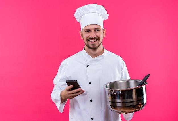 전문 남성 요리사는 흰색 유니폼을 입고 요리사 모자를 들고 빈 냄비와 휴대 전화는 분홍색 배경 위에 유쾌하게 서 웃고