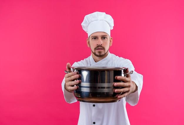 Профессиональный шеф-повар-мужчина в белой форме и поварской шляпе держит пустую кастрюлю, глядя в камеру с серьезным лицом, стоящим на розовом фоне