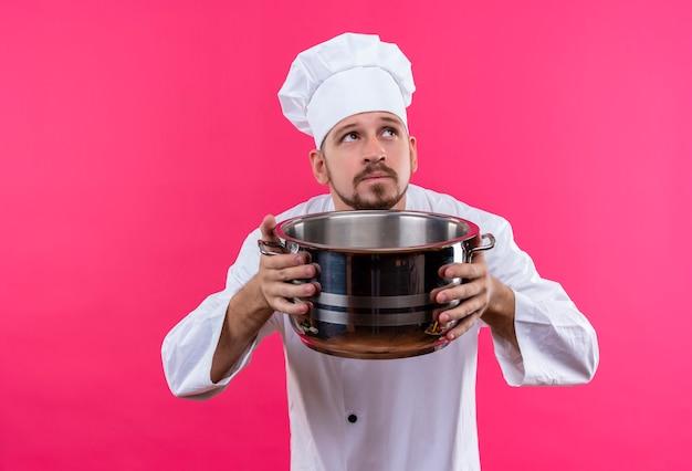 Профессиональный шеф-повар-мужчина в белой форме и поварской шляпе держит пустую кастрюлю, глядя вверх с задумчивым выражением лица, думая, стоя на розовом фоне