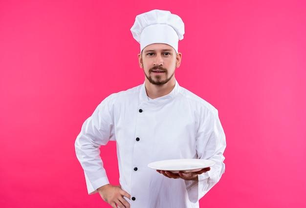 白い制服を着たプロの男性シェフが調理し、ピンクの背景の上に立って自信を持って笑顔でカメラを見て空のプレートを保持している帽子を調理します。