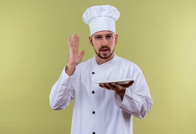 白い制服を着たプロの男性シェフが調理し、緑の背景の上に立って手を上げる空のプレートを保持している帽子を調理します。