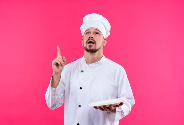 白い制服を着たプロの男性シェフが調理し、ピンクの背景の上に立っているタスクに焦点を当てた指で上向きの空のプレートを保持している帽子を調理します。