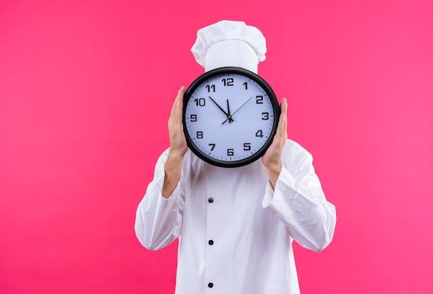白い制服を着たプロの男性シェフが調理し、ピンク色の背景の上に立ってそれの後ろに隠れて大時計を保持している帽子を調理します。