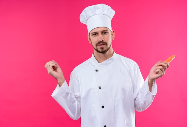 Профессиональный шеф-повар-мужчина в белой форме и поварской шляпе держит морковь, глядя в камеру с улыбкой на лице, стоя на розовом фоне