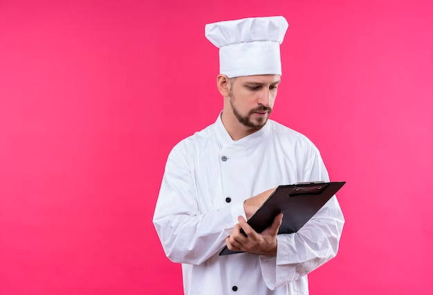 白い制服を着たプロの男性シェフが調理し、ピンクの背景の上に立っている深刻な顔でそれを見てクリップボードを保持している帽子を調理します。