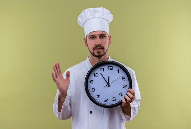Профессиональный шеф-повар-мужчина в белой униформе и поварской шляпе держит часы, поднимая руку, глядя неуверенно, стоя на зеленом фоне