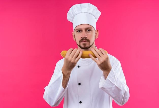 白い制服を着たプロの男性シェフが調理し、ピンクの背景の上に自信を持って立っているトウモロコシを保持している帽子を調理します。