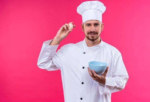 Профессиональный шеф-повар-мужчина в белой форме и поварской шляпе с яйцом и миской смотрит в камеру с улыбкой на лице, стоя на розовом фоне