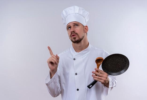 プロの男性シェフが白い制服で調理し、フライパンと物思いに沈んだ表情で白い背景の上に立って人差し指を探している木のスプーンを保持している帽子を調理します。