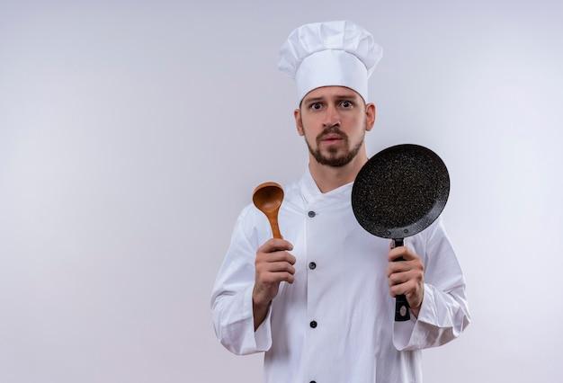白い制服を着たプロの男性シェフが調理し、フライパンと白い背景の上に立って心配して見ている木のスプーンを保持している帽子を調理します。