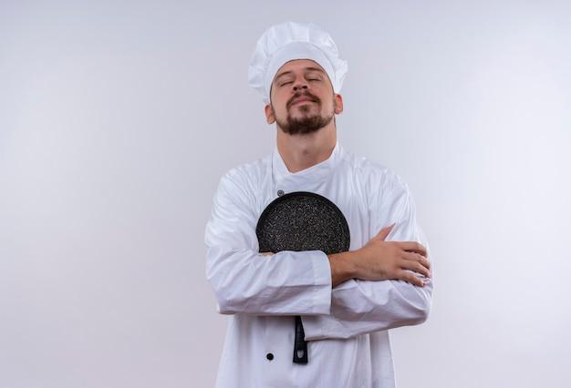 白い制服を着たプロの男性シェフが調理し、自信を持って、白い背景の上に立って満足しているフライパンを保持している帽子を調理します。
