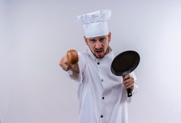 白い制服を着たプロの男性シェフが調理し、怒っている顔が白い背景の上に立ってカメラを指しているフライパンを保持している帽子を調理します。