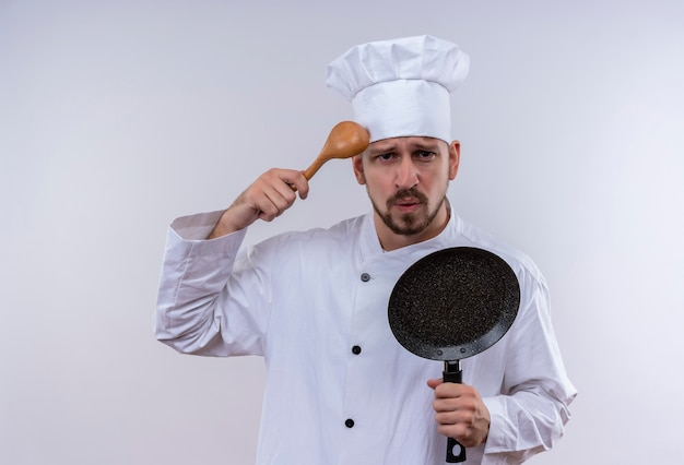 白い制服でプロの男性シェフが調理し、白い背景の上に立って混乱している木のスプーンでフライパンのスクラッチヘッドを保持している帽子を調理します。
