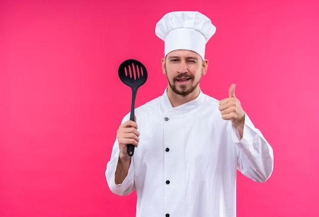 プロの男性シェフが白い制服を着て調理し、ピンクの背景の上に立って親指をウインクし、親指を見せて笑ってカメラを見て取鍋を保持している帽子を調理します。