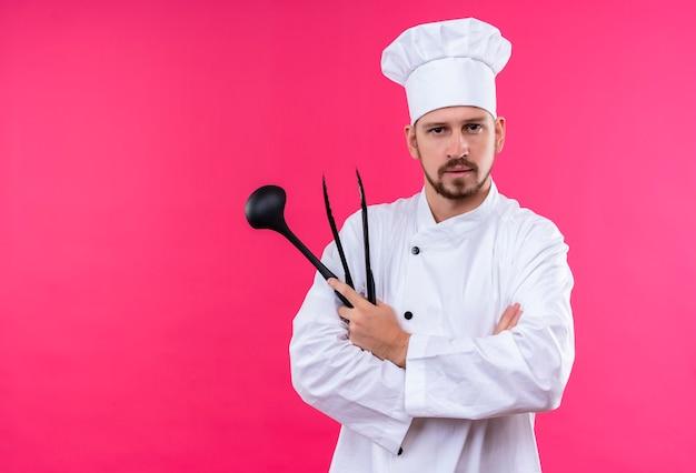 Профессиональный шеф-повар-мужчина в белой форме и поварской шляпе держит ковш, глядя в камеру с серьезным лицом, стоящим на розовом фоне