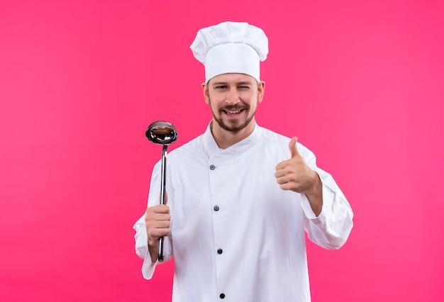 プロの男性シェフが白い制服を着て調理し、ピンクの背景の上に立って親指を示す笑みを浮かべてウインクをしている鍋を保持している帽子を調理します。