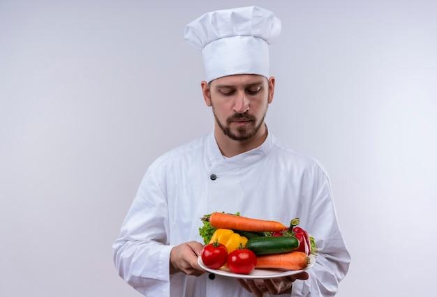 Профессиональный шеф-повар-мужчина в белой форме и поварской шляпе держит тарелку с овощами, глядя на них с серьезным лицом, стоящим на белом фоне