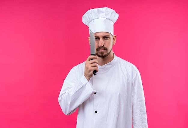 プロの男性シェフが白い制服で調理し、ピンクの背景の上に立っている深刻な顔でカメラを見て彼の顔の近くに鋭いナイフを持って帽子を調理します。