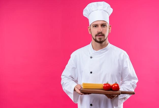 白い制服を着たプロの男性シェフが調理し、トマトとトウモロコシのピンクの背景の上に立って木製のまな板を保持している帽子を調理します。