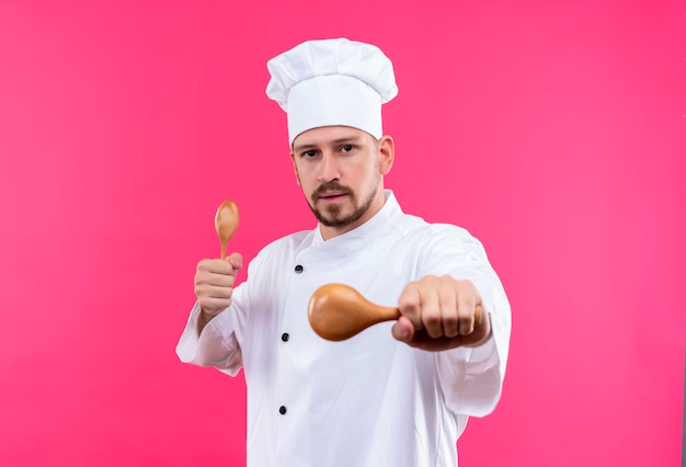 プロの男性シェフが白い制服を着て調理し、ピンクの背景の上に立っている深刻な顔でカメラを見て木製のスプーンを保持している帽子を調理します。