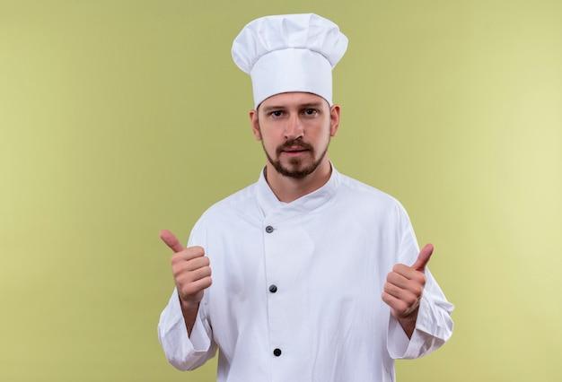 Профессиональный шеф-повар-мужчина в белой униформе и поварской шляпе, глядя в камеру, показывает палец вверх, стоя на зеленом фоне