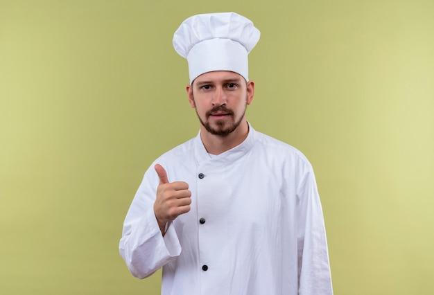 白い制服を着たプロの男性シェフが調理し、緑の背景の上に立って親指を示すカメラを見て帽子を調理します。