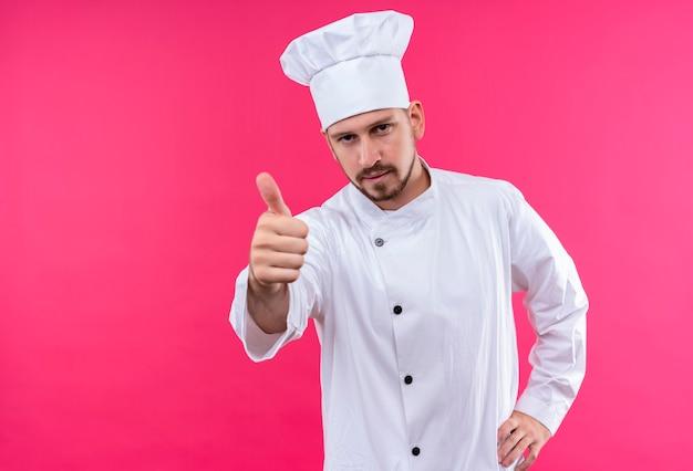 白い制服を着たプロの男性シェフが調理し、ピンクの背景の上に立って親指を示すカメラを見て帽子を調理します。