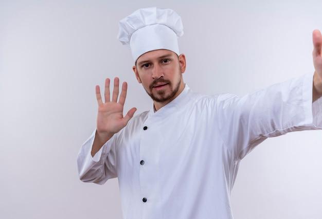 Профессиональный шеф-повар-мужчина в белой форме и поварской шляпе, глядя в камеру, улыбаясь дружелюбно машет рукой, стоя на белом фоне