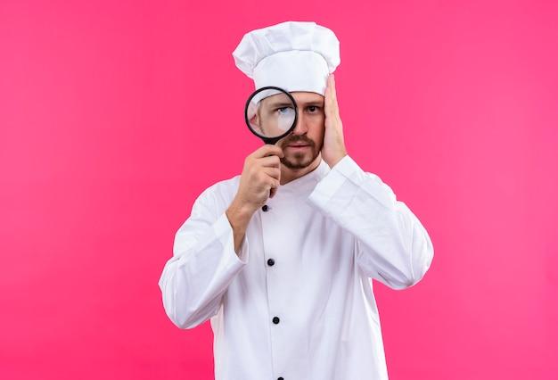 白い制服を着たプロの男性シェフが調理し、ピンクの背景の上に立っている虫眼鏡を通してカメラを見て帽子を調理します。