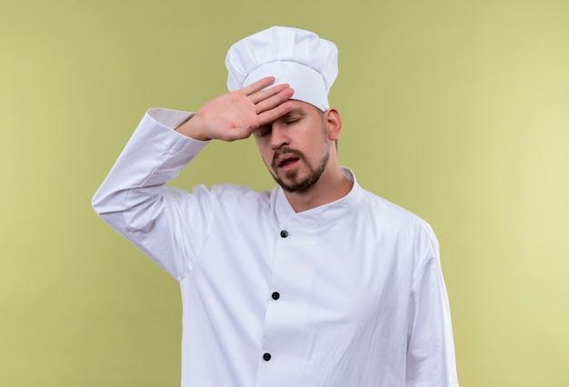Профессиональный шеф-повар-мужчина в белой униформе и поварской шляпе выглядит уставшим и перегруженным, касаясь его головы, стоящей на зеленом фоне