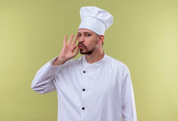 緑の背景の上に立っているジッパーで口を閉じるとプロの男性シェフが白い制服で調理し、帽子マキンフ沈黙ジェスチャーを調理