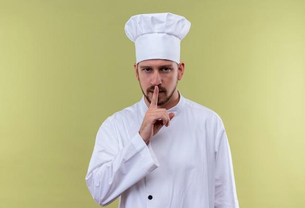 Профессиональный шеф-повар-мужчина в белой форме и поварской шляпе делает жест молчания с пальцем на губах, стоя на зеленом фоне