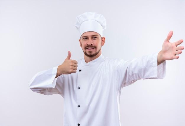 白い制服を着たプロの男性シェフが調理し、白い背景の上にフレンドリーな立っている笑顔を親指を示す歓迎のジェスチャーを作る帽子を調理します。